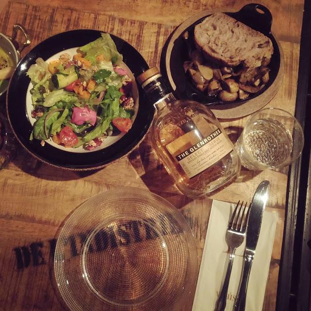 בתמונה: בקבוק וויסקי גלנרוטס מונח על השולחן לצד שתי מנות אוכל. צילום: יחסי ציבור