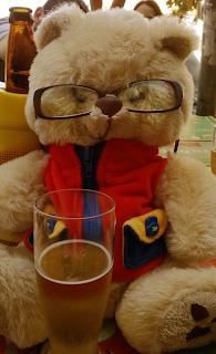 ursinho de pelúcia com óculos e um copo de cerveja