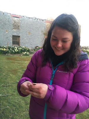 A woman with a large smile on her face holding a very small slow worm