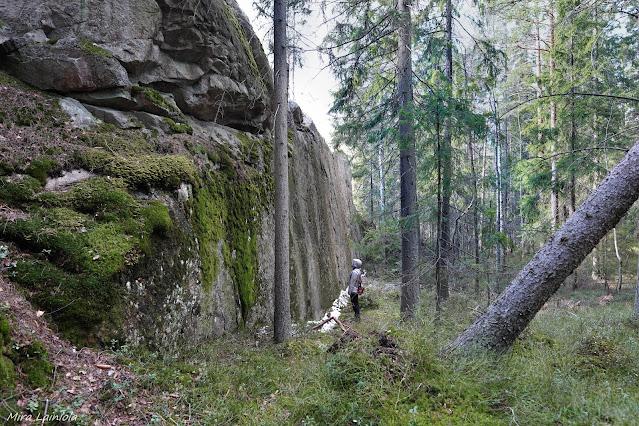 Nainen pystysuoran kallioseinämän edessä metsässä