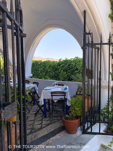 Tables decked in white table cloths in a vaulted whitewashed courtyard restaurant tiled with pebbles in front of a mountain range.