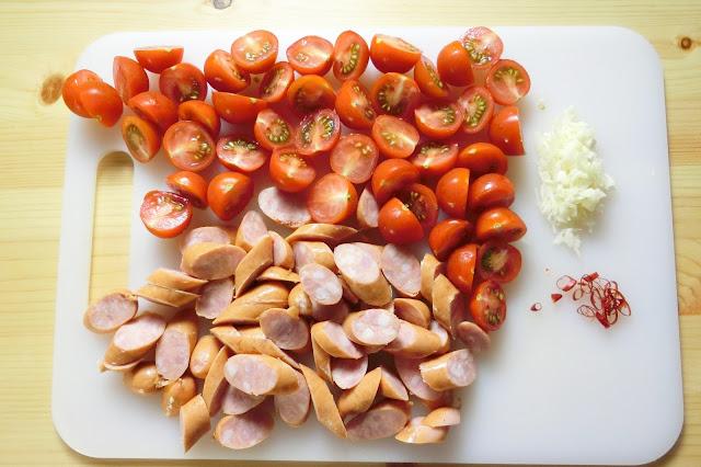 チェリートマトは半分に切り、ウィンナーは2㎝幅の斜め切りにします。  にんにくはみじん切りにし、赤とうがらしは種を取り除いてから薄い輪切りに切ります。