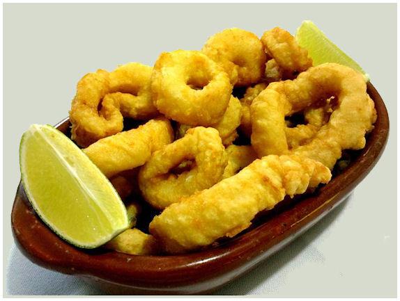 Ruoka-annos friteerattuja mustekalan lonkeroista leikattuja renkaita ja sitruunaviipale. Herkullinen näky.