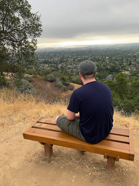 White teen boy with short brown hair wearing a baseball cap, seen from behind, sitting on a wooden park bench overlooking the San Francisco Bay.