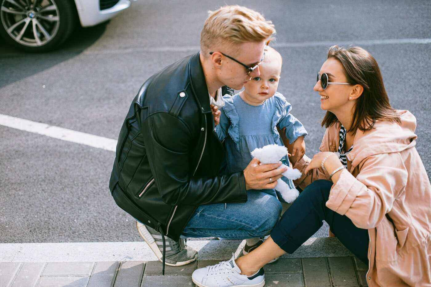 man and woman sitting on street curb with baby - free parenting tools