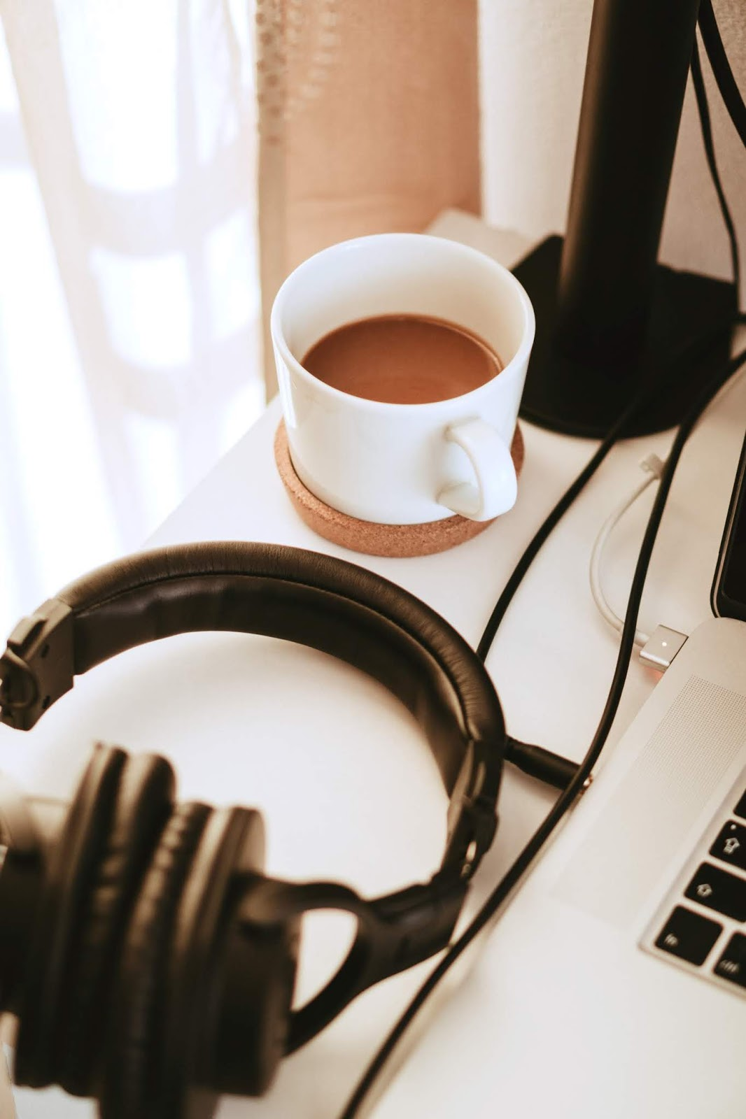 Image is of a coffee mug and black headphones, on a white desk. In the background, a brown curtain and white sheer underlay is visible. The base of a black desk lamp and corner of a laptop is also partially visible.