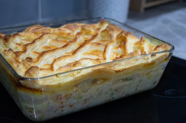 A chicken and vegetable pie in a glass oven dish