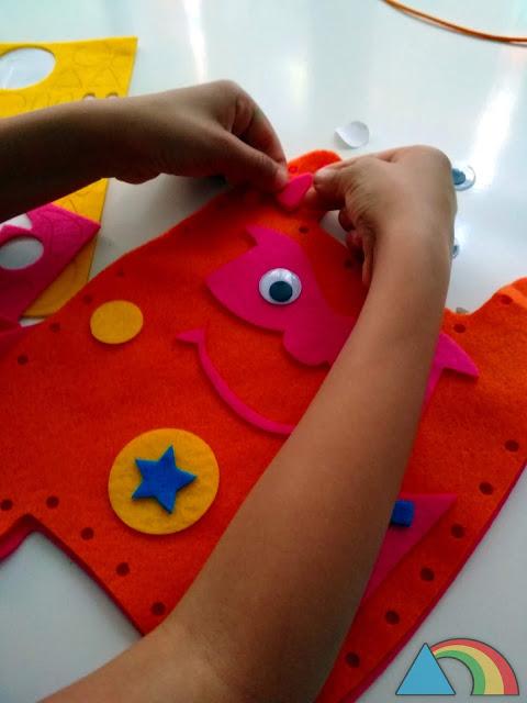 Decorando monstruito de fieltro con piezas precortadas y encoladas de fieltro de colores