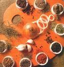 Especias y hierbas aromáticas. Paleta de condimentos con nueve pocillos pequeños. En el centro, varios dientes de ajo y media cebolla cortada junto a cuatro aritos.