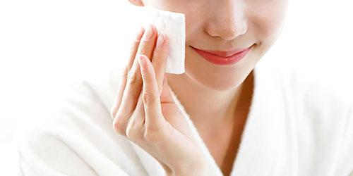Chica limpiando su rostro con agua micelar