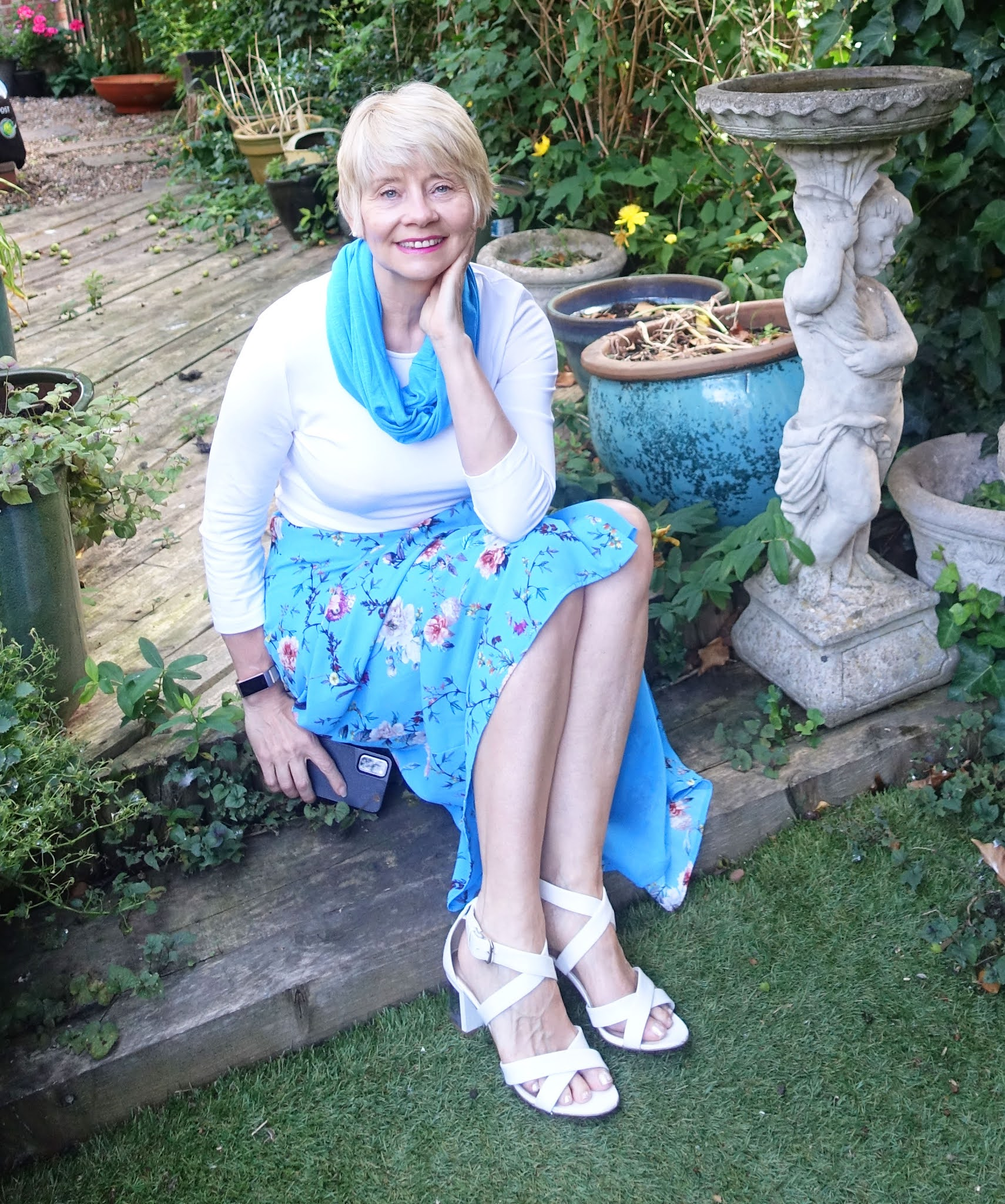 Over 60 style blogger Gail Hanlon from Is This Mutton in Chinese blue floral skirt worn with white top and infinity scarf from Kettlewell Colours