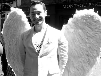 Blck and White photo of a young man dressed in white with white feather wings