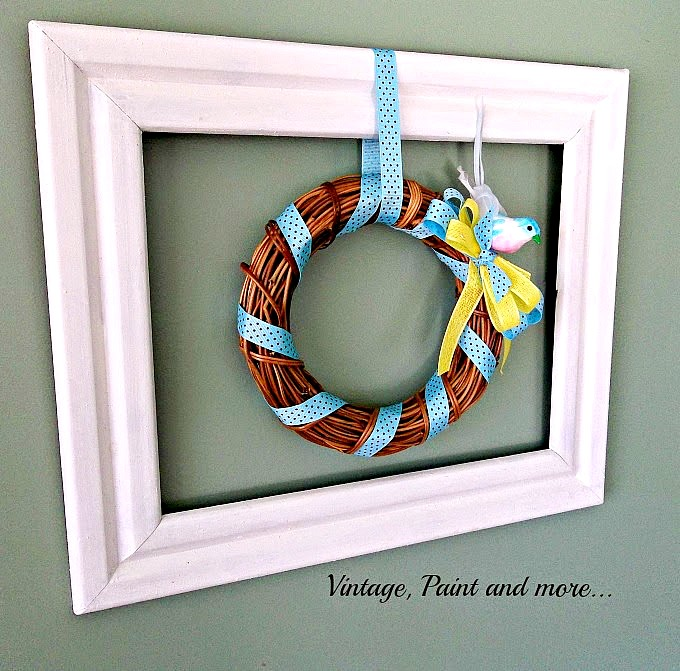 Vintage Paint and more... a grapevine wreath done in a blue and yellow theme hanging in a wooden picture frame for Spring