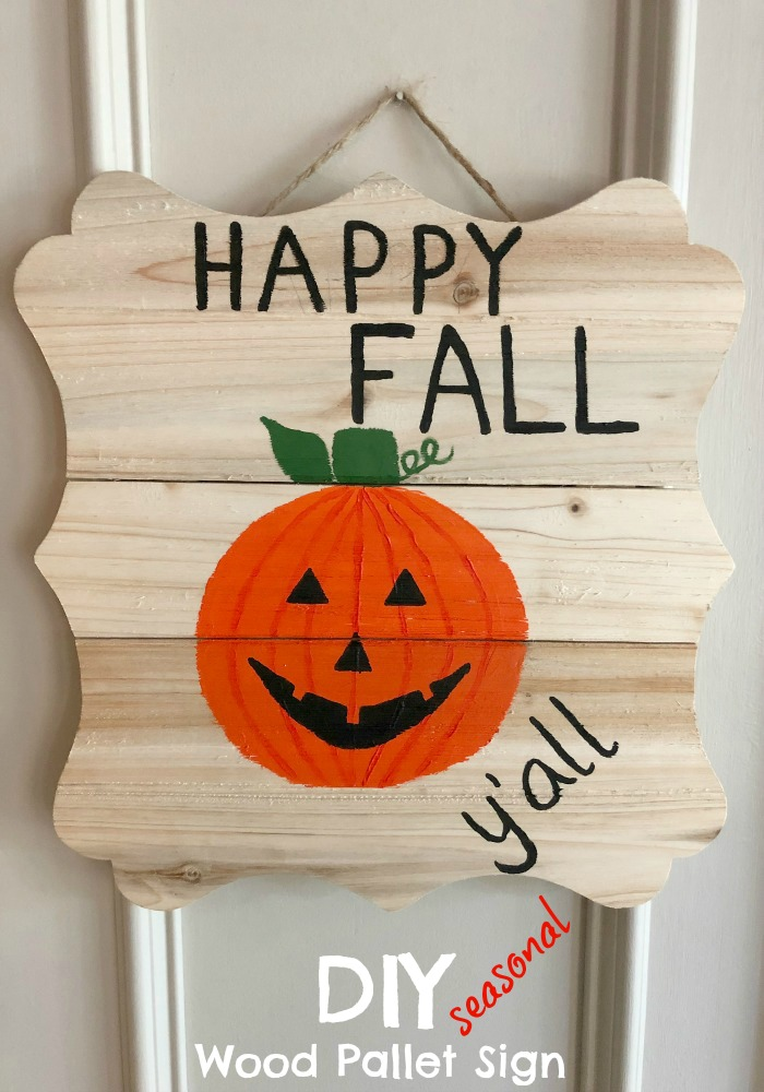 Wood pallet wall sign that reads happy fall y'all in black lettering with an orange jack o lantern that's smiling