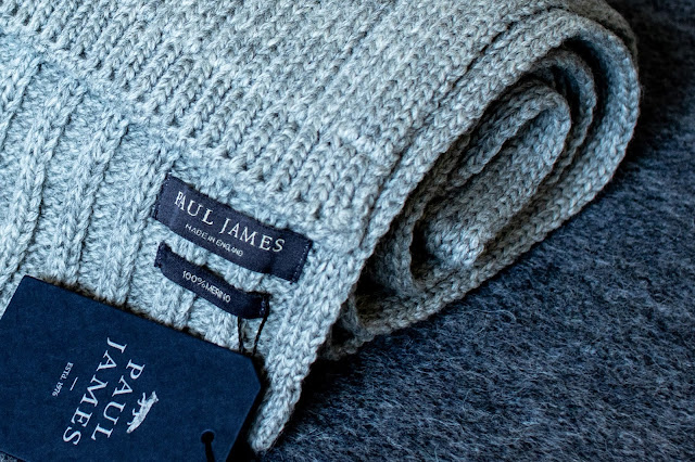 Grey merino wool scarf rolled up and showing the label saying Paul James