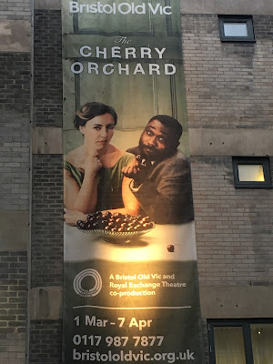 Photo of banner on outside of theatre, showing Kirsty Bushell as Ranyevskaya, and Jude Owusu as Lopakhin, and a bowl of cherries
