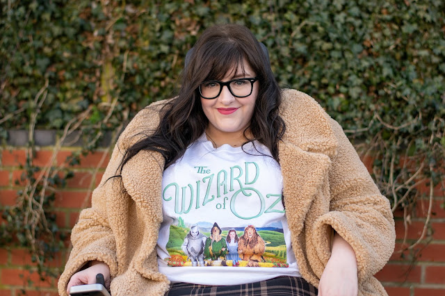 Close up of woman sat in wheelchair wearing Wizard of Oz tshirt and cream teddy coat