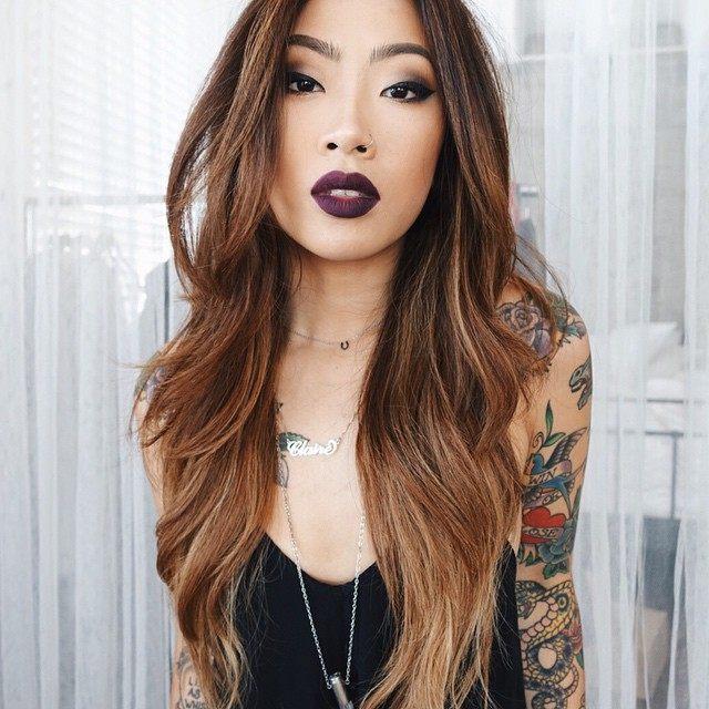 Foto de chica asiática con tatuaje tradicional en brazos