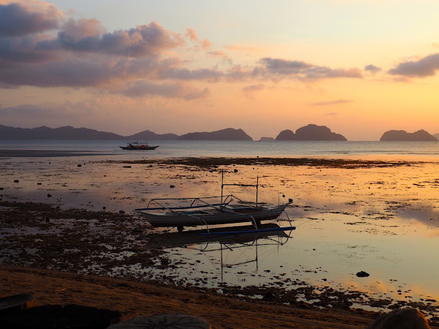 Boat in the shallows at sunset at Corong Corong Beach, near El Nido, Palawan, Philippines