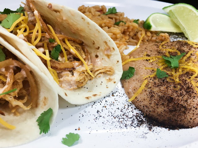 A close up of our on the border southwest chicken tacos on flour tortillas with our creamy refried beans and mexi-rice.