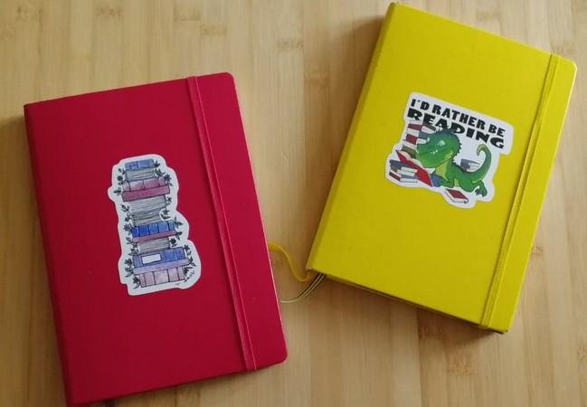 """Deux carnets (1 grenat avec une image de livres et 1 jaune avec noté """"I'd rather be reading"""") posés sur une table."""