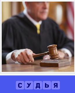 судья на процессе за столом и с молотком в руке