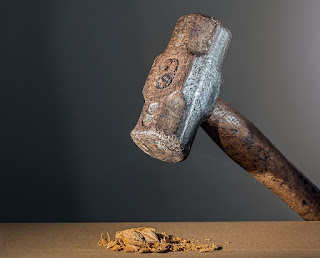 Image shows a heavy hammer held over a crushed nut.