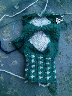 A mitten on the needles.  The cuff is stranded colourwork and ribbing, while the back of the hand shows an intarsia geometric diamond.