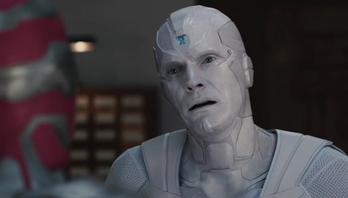 Imagem: O visão branco, ele  é um robô meio humano com partes metalizadas mecânicas e partes humanas e ele é todo branco e careca e em sua testa tem uma um chip azul que brilha. Ele está olhando com cara de confuso e receoso.
