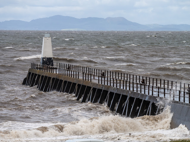 Photo of white-topped waves around Maryport pier with the Scottish hills in the distance
