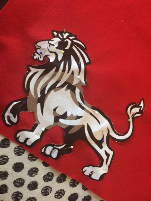 Paper lion pinned to red fabric