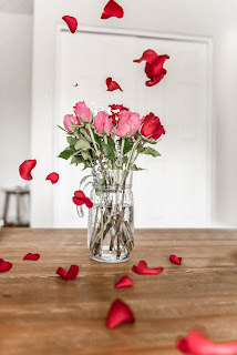 Red and pink long-stemmed roses in a glass vase on a wooden table with a white wall behind, There are petals floating in the air around the vase.