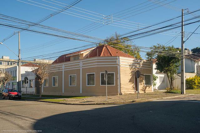 Casa de esquina com faixas decorativas e mansarda.