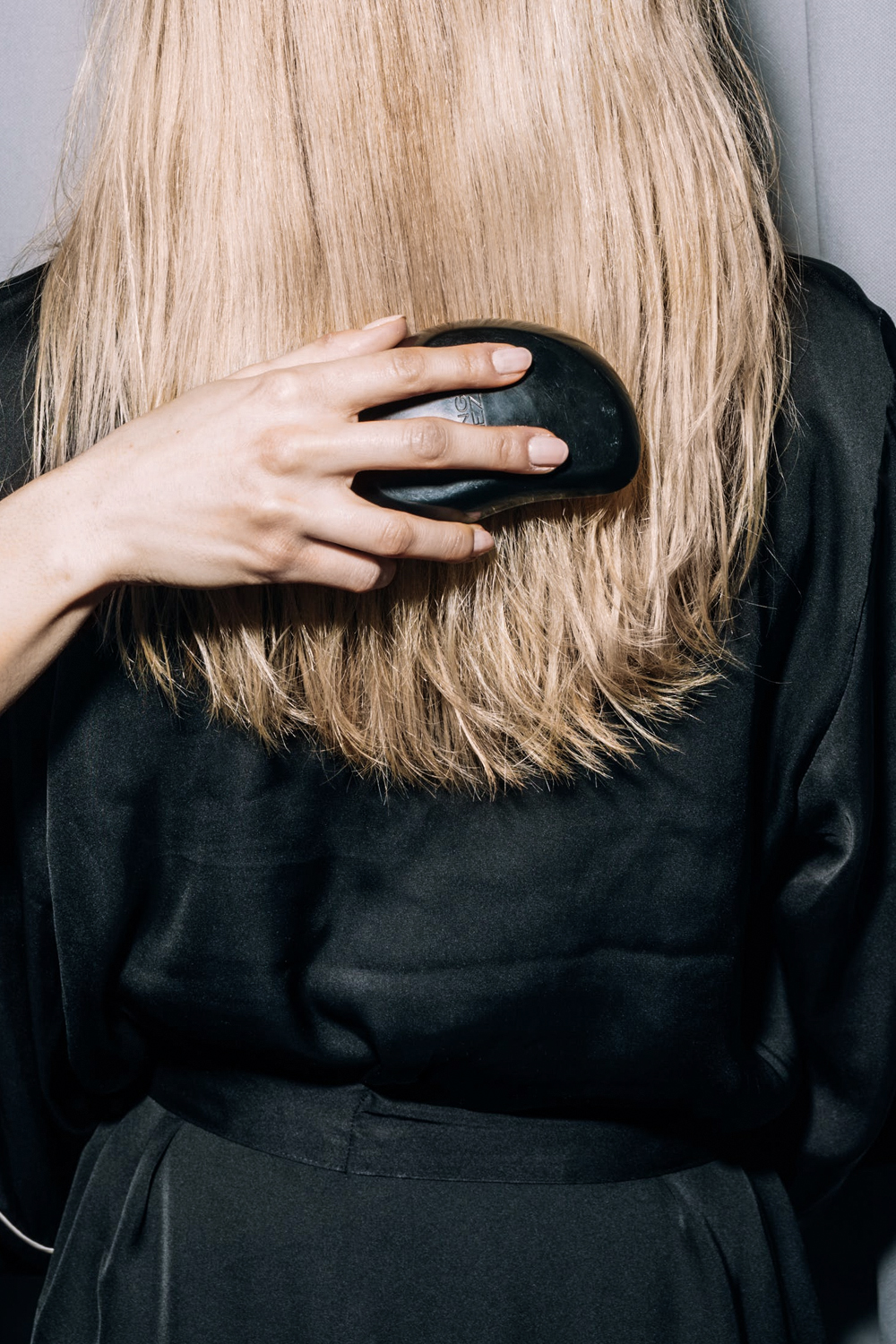 a hand combs womens hair, a view from the back