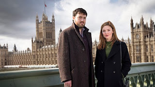 Tom Burke as Cormoran Strike and Holliday Grainger as Robin Ellacott in front of the Houses of Parliament in London