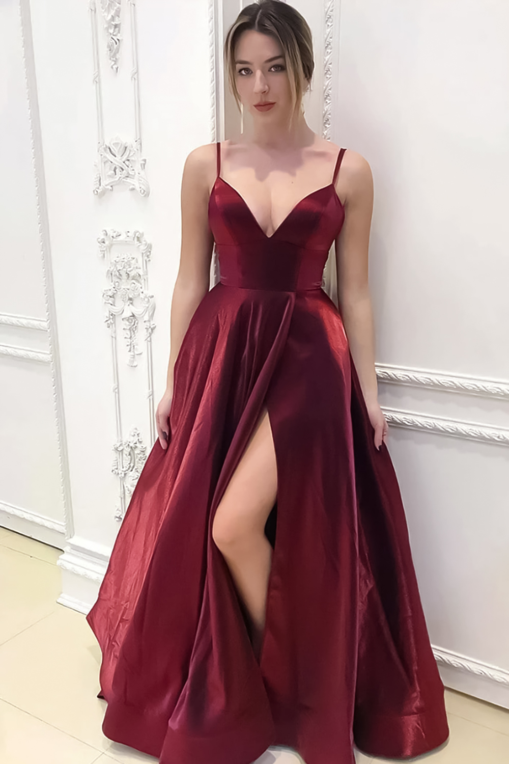 woman in a floor-lengh evening dress is posing in the ball room