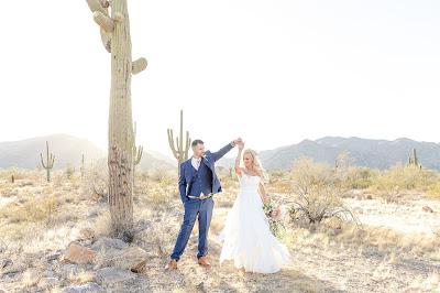 bride and groom dancing in the desert
