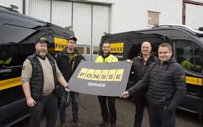 Medarbetarna vid Ponsse i Uddevalla samlade vid företagsbilar och med företagsskylt i sina händer.
