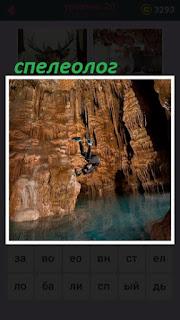 в пещере спускается спелеолог к воде внизу