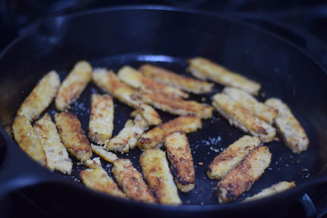 The sliced tempeh browned in a pan on the stove.
