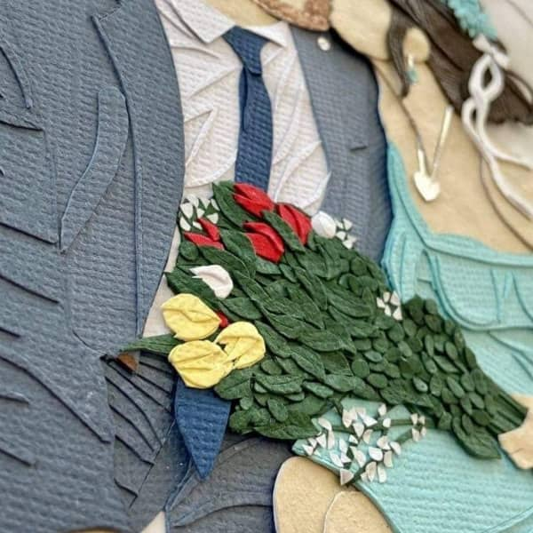 detail of paper art couple with flower bouquet on woman's lap
