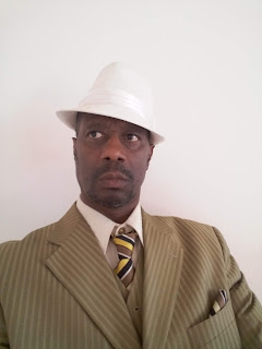 Picture of the author of the book, wearing a suit & tie and a white felt hat