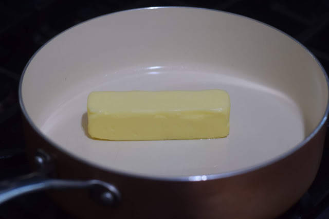 A stick of butter in a pan on the stove.