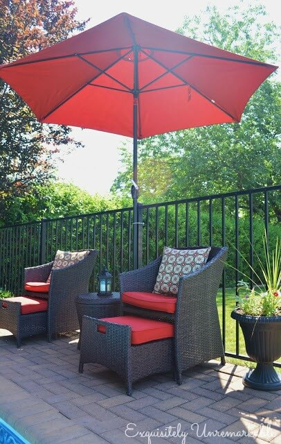 Chairs with red cushions and red umbrella by pool