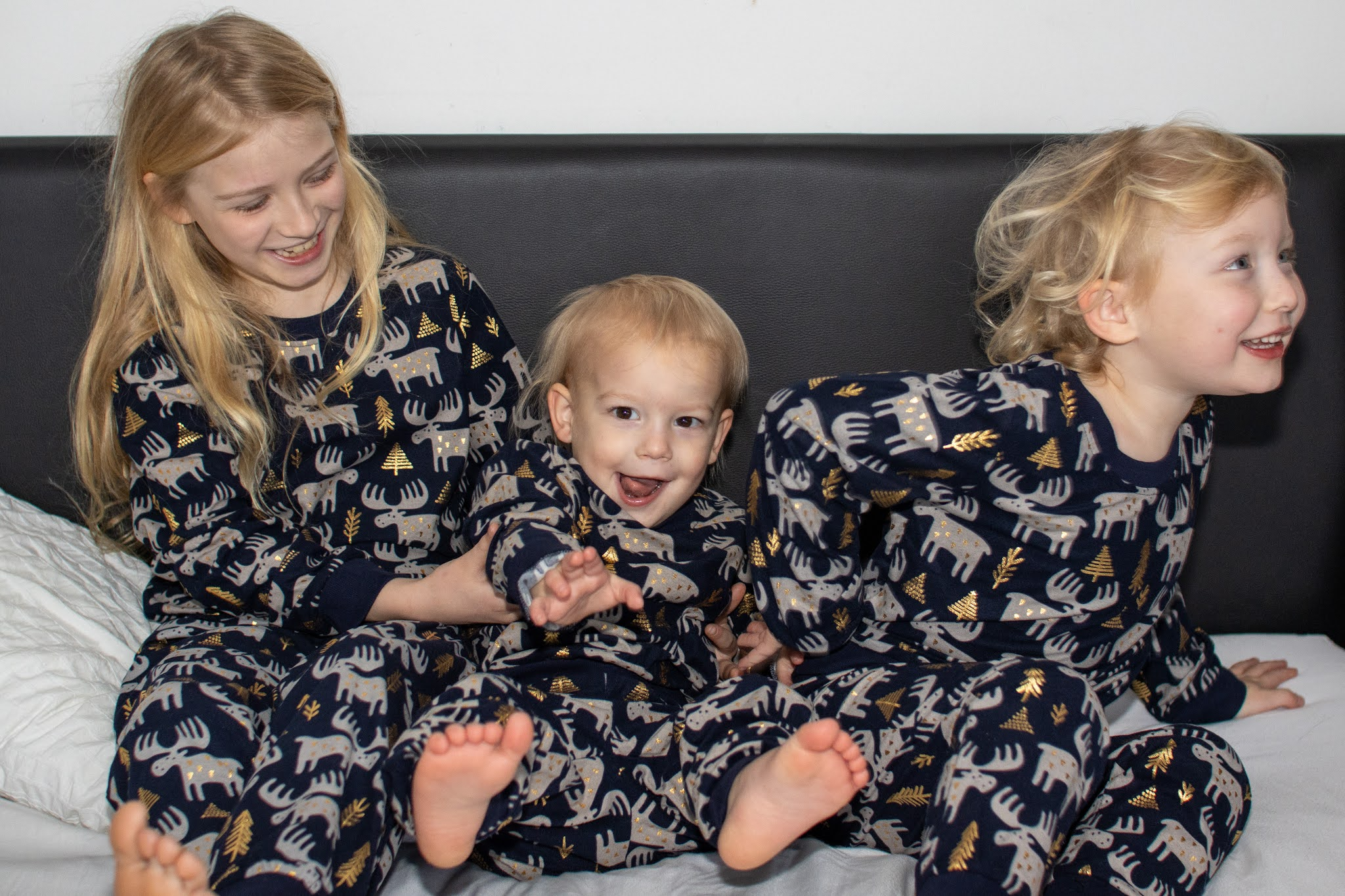 3 siblings on a bed in matching Christmas pyjamas. The oldest sibling splits her time between parents houses