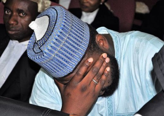 Shamsudeen Bala Mohammed hiding his face in court after being charged by the efcc
