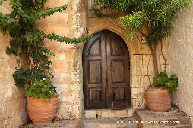 The dark wooden entrance door of a soft red-beige stone house framed by green plants.