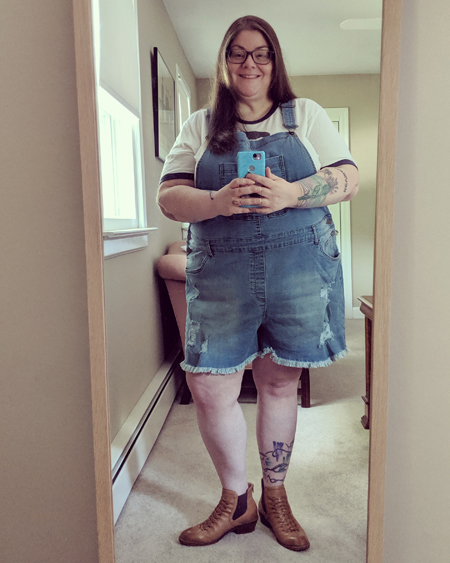 image of me standing in a full-length mirror smiling, with my hair down, wearing grey-framed glasses, a white t-shirt with black trim, medium-wash blue denim overalls, and tan ankle boots