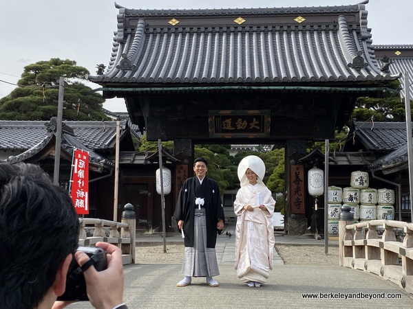 a bridal couple poses for pictures outside Zenkoji Temple in Nagano City, Japan