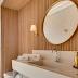 Banheiro com pórtico de madeira na área da bancada, espelho redondo e metais dourados!